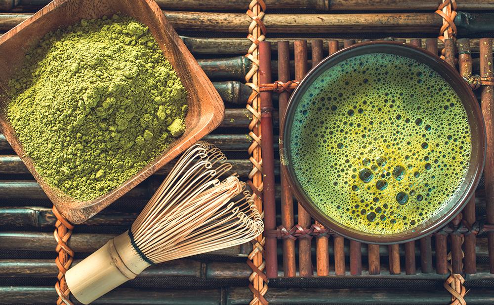 Чашечка зеленого чая матча, сухой порошок матчи и венчик для взбивания и приготовления чая матча